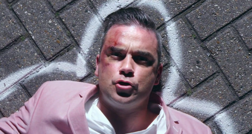Robbie Williams wearing pink suit in Candy video