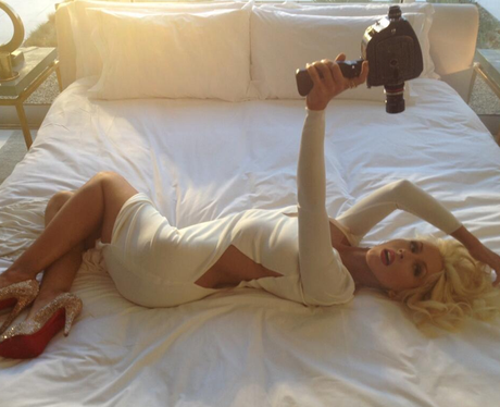 Christina Aguilera lying on a bed filming her new advert