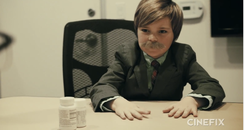A boy wearing a suit and fake moustache