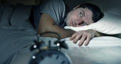 Man waking up with alarm clock