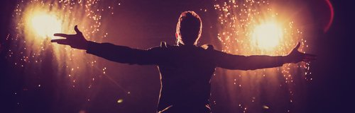 Olly Murs performing on stage with fireworks