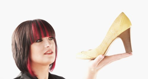 Woman holding up a high heeled shoe